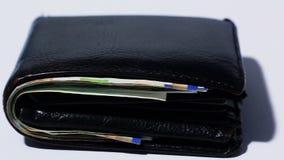 Stack of various of israeli shekel money bills in close black leather wallet - Pan left stock footage