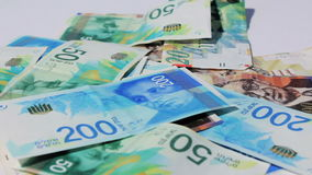 Stack of various of israeli shekel money bills  - Pan left stock footage