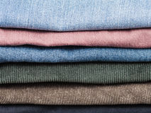 Stack of various jeans and corduroy slacks Royalty Free Stock Photography