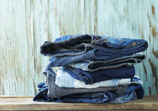 Stack of various jeans on  wooden background Stock Image