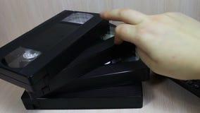 Stack of VHS video tape cassette. Female hand touches stack of VHS video tape cassette stock footage