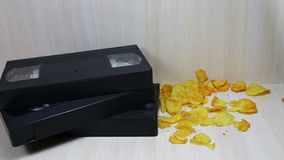 Stack of VHS video tape cassette and potato chips. TV remote. stack of VHS video tape cassette and falling potato chips stock video