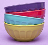 Stack of Vibrant Bowls. Stack of vibrant colored bowls on a purple background stock photos