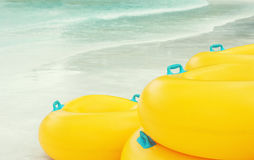 Stack of vibrant yellow Inflatable tubes at beach. Stack of vibrant yellow Inflatable tubes at the white sand beach. Blurred blue-green water in background royalty free stock photos