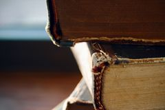 A stack of vintage old beat-up books lying spine forward stock images