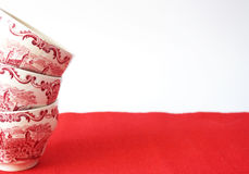 Stack of vintage tea cups in a red carpet- Detail. Detail of stack of vintage tea cups in a red carpet Royalty Free Stock Photos