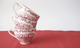 Stack of vintage tea cups on red table Royalty Free Stock Photos