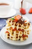 Stack of waffles with banana, strawberry and flowing chocolate royalty free stock images