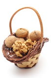 Stack of walnuts in wicker basket on white background Royalty Free Stock Image