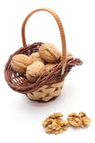 Stack of walnuts in wicker basket on white background Royalty Free Stock Images