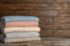 Stack of warm autumn clothes on wooden table. Space for text stock images