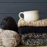 Stack of warm clothes from knitted knitwear with a cup of coffee Royalty Free Stock Photo
