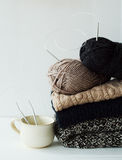 Stack of warm clothes from knitted knitwear with a cup of coffee Royalty Free Stock Photos