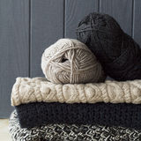 Stack of warm clothes from knitted knitwear over grey wooden bac Royalty Free Stock Photos