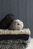 Stack of warm clothes from knitted knitwear over grey wooden bac. Stack of clothes from knitted knitwear over grey wooden background Royalty Free Stock Image