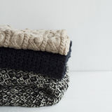 Stack of warm clothes from knitted knitwear over white backgroun Stock Photo