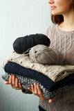 Stack of warm clothes from knitted knitwear in woman's hands Royalty Free Stock Photography