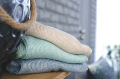 A stack of warm clothes. A stack of warm clothes in pastel colors. In the background is a cozy conat royalty free stock photos