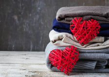 Stack of warm knitted clothes. Sweaters and heart. Selective focus Royalty Free Stock Photography