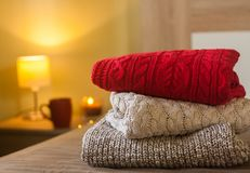 Stack of warm knitted sweaters on a bed decorated with lights and lamp, cup and candle in the background royalty free stock photo