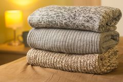 Stack of warm knitted sweaters on a bed. Small lamp in the background royalty free stock photo