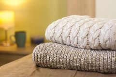 Stack of warm knitted sweaters on a bed. Small lamp in the background royalty free stock image