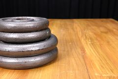 Weight plates. A stack of weight plates on a wooden table Royalty Free Stock Photo