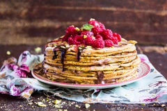 Stack of wheat golden pancakes or pancake cake with freshly picked raspberry, chopped pistachios, chocolate sauce on a dessert pla Royalty Free Stock Image