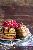 Stack of wheat golden pancakes or pancake cake with freshly picked raspberry, chopped pistachios, chocolate sauce on a dessert pla Royalty Free Stock Photos