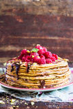 Stack of wheat golden pancakes or pancake cake with freshly picked raspberry, chopped pistachios, chocolate sauce on a dessert pla Stock Image