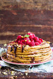 Stack of wheat golden pancakes or pancake cake with freshly picked raspberry, chopped pistachios, chocolate sauce on a dessert pla Royalty Free Stock Images