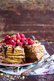 Stack of wheat golden pancakes or pancake cake with freshly picked raspberry, chopped pistachios, chocolate sauce on a dessert pla Stock Photos