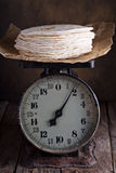 Stack of wheat tortillas on vintage kitchen scales Royalty Free Stock Photography