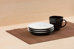 Stack of the white and black plates near black cup on tablemat. Royalty Free Stock Photography