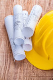 Stack of white blueprints and yellow hardhat on Royalty Free Stock Photos