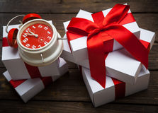 Stack of white Christmas presents on dark wood background Royalty Free Stock Photos