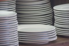 Stack of white clean dishes placed on wooden shelf to prepare for buffet in the morning. Soft focus. Close up stack of white clean dishes placed on wooden shelf Royalty Free Stock Image