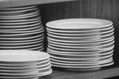 Stack of white clean dishes placed on wooden shelf to prepare for buffet in the morning. Soft focus. Close up stack of white clean dishes placed on wooden shelf Royalty Free Stock Images