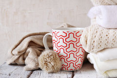Stack of white cozy knitted sweaters next to cup of coffee on a wooden table. Stock Photo
