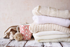 Stack of white cozy knitted sweaters next to cup of coffee on a wooden table. Royalty Free Stock Images