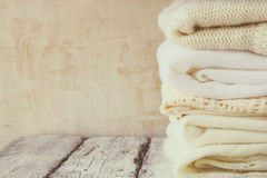 Stack of white cozy knitted sweaters on a wooden table Stock Photography