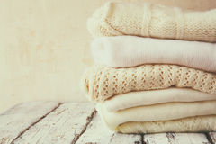 Stack of white cozy knitted sweaters on a wooden table Royalty Free Stock Images