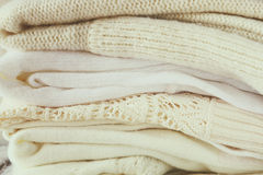 Stack of white cozy knitted sweaters on a wooden table Royalty Free Stock Photo