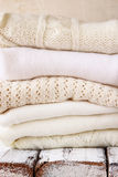 Stack of white cozy knitted sweaters on a wooden table Stock Photos