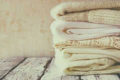 Stack of white cozy knitted sweaters on a wooden table Royalty Free Stock Image