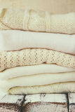 Stack of white cozy knitted sweaters on a wooden table Royalty Free Stock Photos