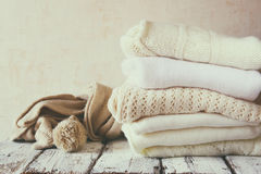 Stack of white cozy knitted sweaters on a wooden table Royalty Free Stock Photography