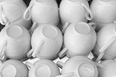 The stack of the white cups of tea in the shelf Royalty Free Stock Photos