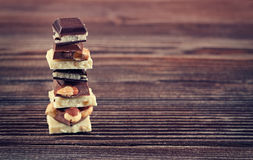 Stack of white, dark and milk chocolates on wooden table Stock Image