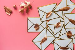 Stack of white envelopes with golden leaves on blush pink background with copy space royalty free stock photo